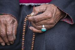 Old Tibetan woman holding buddhist rosary in Hemis monastery, Ladakh, India. Hand, turquoise ring and rosary, close up. Old hands with turquoise ring of a royalty free stock photos