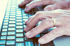 Old hands typing Royalty Free Stock Image
