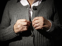 Old hands. Of an unrecognizable senior woman buttoning her self royalty free stock images
