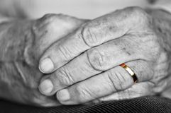 Old hands with wedding band. Close up on elderly woman hands with golden wedding ring royalty free stock photo