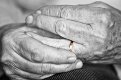 Old hands with wedding band. Close up on elderly woman hands with golden wedding ring royalty free stock photography