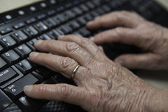 Old hands writing on keyboard. Old woman writing at a computers keyboard. Could be used as a metaphor for retirement plan Stock Images