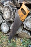 Old handsaw resting on a pile of wooden lumber. Rural lifestyle concept stock photography