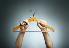 Old Hanger. Man holding an old wooden clothes hanger in his hands Royalty Free Stock Image