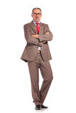 Old happy businessman standing with hands crossed. Full body picture of an old happy businessman wearing glasses standing with hands crossed on white background Stock Photo