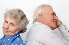 Old happy couple sitting back to back Stock Image