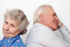 Old happy couple sitting back to back stock image