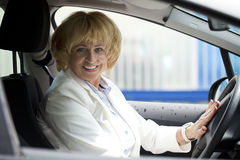 Old happy elderly driver woman 55-60 years in jacket Driving a C Stock Images
