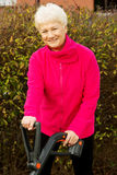 An old happy lady mowing in the garden. Outdoor background stock image