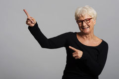 An old happy lady pointing on a copy space. Stock Photography