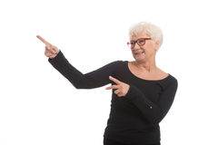 An old happy lady pointing on a copy space. Stock Image