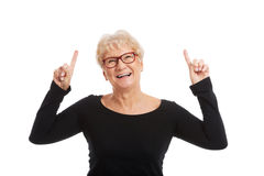 An old happy lady pointing on a copy space. Royalty Free Stock Images