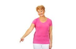 An old happy lady pointing for something.  Stock Images