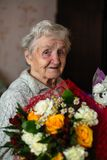 An old happy woman with a bouquet of flowers. stock images