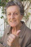 An old happy woman shows that she is satisfied and happy with her life Royalty Free Stock Images