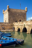 Old harbor. Blue fishing boats with stone walls and battlement on old port in Essaouira, Morocco, Africa Royalty Free Stock Image