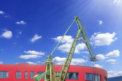 Old harbor crane in front of a modern day office building Stock Photo