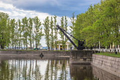 The old harbor crane of the XIX century  in Kronstadt, Russia. The old harbor crane  of the XIX century on the bank of Italian pond in Kronstadt, Russia Royalty Free Stock Photos