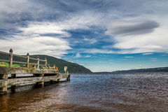 Old harbor over Loch Ness in sunny Scotland Stock Photos