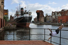 Gdansk harbor with steamer. Old Motlawa canal of the old harbour with an old steamer and middle-age crane on the right, training gymnast in the foreground. City Stock Photos