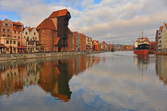 Old harbour canal in Gdansk. One bank of old harbour canal of Motlawa in Old City of Gdansk, Poland in sunny winter day. An old steamer of 1948 on the right Stock Photos