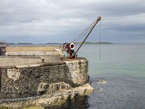 The old harbour and winch Portrush Ireland. View of an old harbour complete with loading winch Stock Image