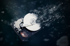 The old hard disk drive is disintegrating in space. Conception of passage of time and obsolete technology Royalty Free Stock Photo