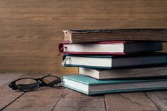 Old hardback books with glasses on wooden table. royalty free stock photo