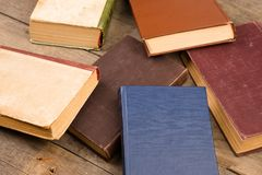 Old hardback books or text books on wooden table. Old and used hardback books or text books on wooden table royalty free stock images