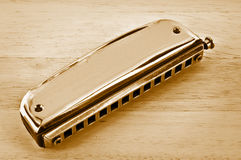 Old harmonica. Old harmonica on the wooden table in vintage style Royalty Free Stock Photo