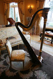 Old harp. A room with a harp in a mansion with antique furniture Stock Photography