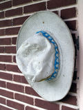 Close-up old and dirty white canvas hat with blue strap hanging on brown brick wall. Construction worker costumes accessories, vertical image royalty free stock images
