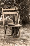 Old Hat and Jacket. Hanging on wooden chair Stock Photo