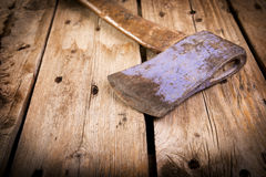 Old Hatchet. An old hatchet axe with a wooden handle and wear marks sits on a rough timber background Stock Photo