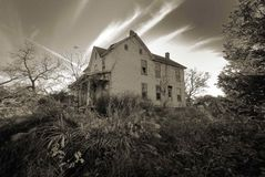 Old haunted farmhouse house. Spooky old haunted farmhouse house with clouds passing by royalty free stock image