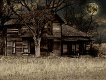 An Old Haunted House. Old Run-down Haunted Farm House with Full Moon - Halloween Night royalty free stock photography
