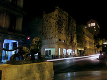Old Havana: Prado street at night. Prado street at night with a bronze lion statue looking to art insects over a building. Havana, Cuba Stock Photos
