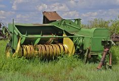 Old hay baler parked in the long grass and weeds Stock Photography