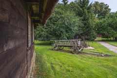 Old hay wagon. Hay wagon in front of traditional wooden cottage in Masuria region of Poland Royalty Free Stock Photo
