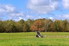Old hay walker in the pasture. An old hay walker is left in a field with a background of trees in the early season of fall Royalty Free Stock Image