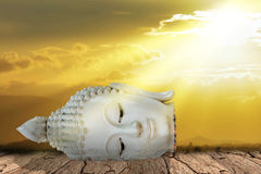 Old head of Buddha statue on cracked ground Royalty Free Stock Image