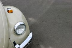 Old Headlight. Vintage car headlight, bumper, against pavement Stock Photo