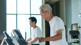 Healthy Asian senior couple exercise together in gym running treadmill. Old healthy Asian senior couple exercise together in gym running treadmill stock photography
