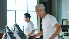 Healthy Asian senior couple exercise together in gym running treadmill royalty free stock images