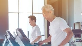 Healthy Asian senior couple exercise together in gym running treadmill. Old healthy Asian senior couple exercise together in gym running treadmill stock images