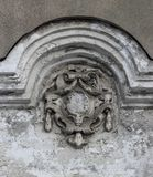 An old and heavily damaged coat of arms as a detail of facade decoration. Closeup of an old and heavily damaged coat of arms Stock Image