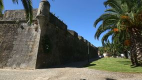 Old high fortifying wall in city with sidewalk along it, panorama and sequence. Stock footage stock footage
