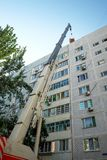 Old high-rise building, crane with cargo and blue sky. Restoration work royalty free stock photography