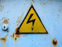 Old high voltage sign on a blue rusty door. Old high voltage sign. Yellow triangle on a blue rusty door. Hazard danger symbol royalty free stock images
