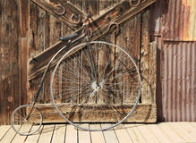 Old High Wheel Bicycle in Front of Whethered Barn Door Royalty Free Stock Photography